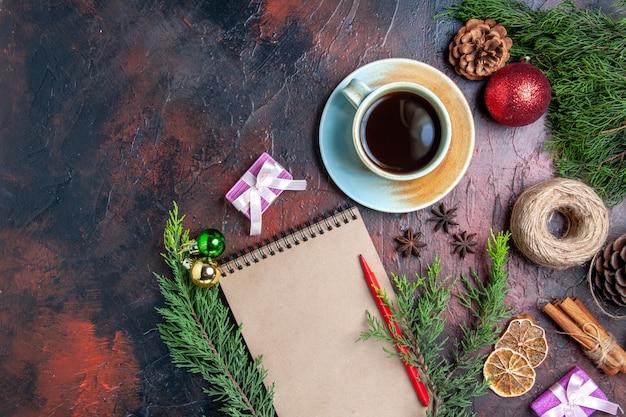 상위 뷰 빨간 펜 노트북 소나무 나뭇 가지 스타 아니스 말린 레몬 슬라이스 진한 빨간색 표면에 차 짚 실 한잔