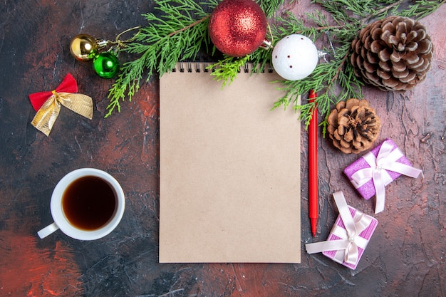 Вид сверху красная ручка блокнот сосновые ветки елочные игрушки и подарки чашка чая на темно-красной поверхности