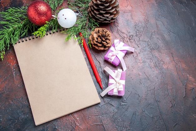 상위 뷰 빨간 펜 노트북 소나무 나무 가지 크리스마스 트리 볼 장난감 및 어두운 빨간색 표면 여유 공간에 선물