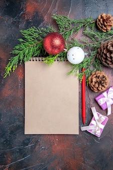 上面図赤ペンノートブック松の木の枝クリスマスツリーボールのおもちゃと濃い赤の表面の贈り物