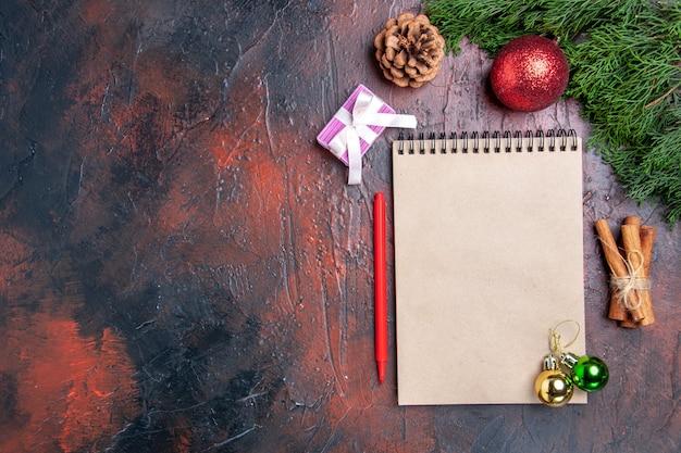 상위 뷰 빨간 펜 노트북 소나무 나무 가지 크리스마스 트리 볼 장난감 계피 스틱 어두운 빨간색 표면 여유 공간 크리스마스 사진
