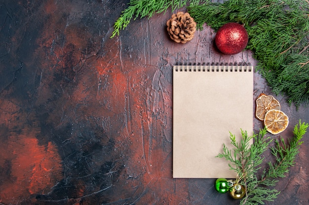 상위 뷰 빨간 펜 노트북 소나무 나무 가지 크리스마스 트리 볼 장난감 말린 레몬 슬라이스 어두운 빨간색 표면 여유 공간 크리스마스에 차 한잔 사진