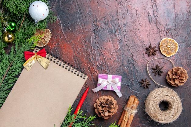 상위 뷰 빨간 펜 노트북 소나무 나무 가지 크리스마스 트리 볼 장난감 짚 스레드 스타 아니스 어두운 빨간색 표면 복사 공간에