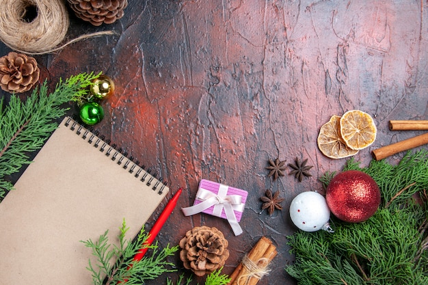 상위 뷰 빨간 펜 노트북 소나무 나무 가지 크리스마스 트리 공 및 선물 계피 아니스 짚 실 말린 레몬 조각 어두운 빨간색 표면 여유 공간에