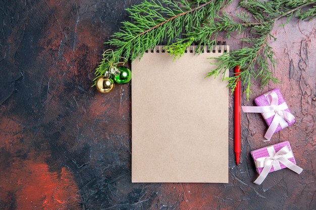 Вид сверху красная ручка блокнот ветки сосны рождественская елка игрушки и подарки на темно-красной поверхности свободное пространство