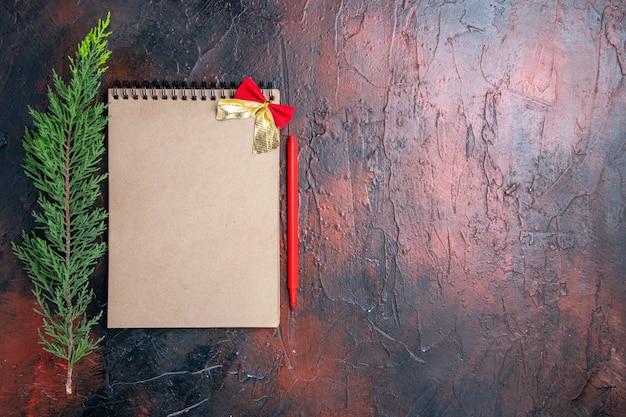 Вид сверху красная ручка блокнот с бантом ветка сосны на темно-красной поверхности с местом для копирования