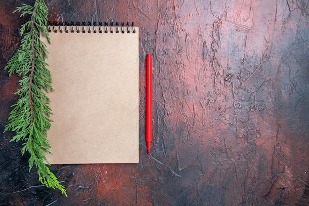 Вид сверху красная ручка блокнот с бантиком ветка сосны на темно-красной поверхности копией пространства