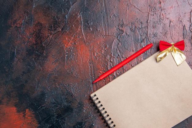 Вид сверху красной ручкой на блокноте с маленьким бантом на темно-красной поверхности с копией пространства