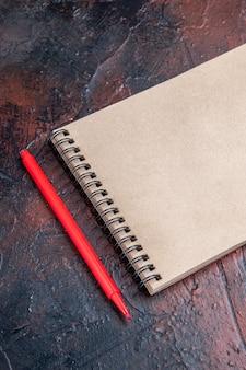 Вид сверху красная ручка блокнот с бантом на темно-красной поверхности