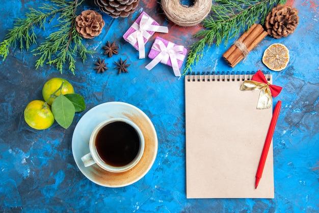 Вид сверху красная ручка лук тетрадь ветки сосны шишки палочки корицы чашка чая анисов соломенная нить мандарины на синей поверхности