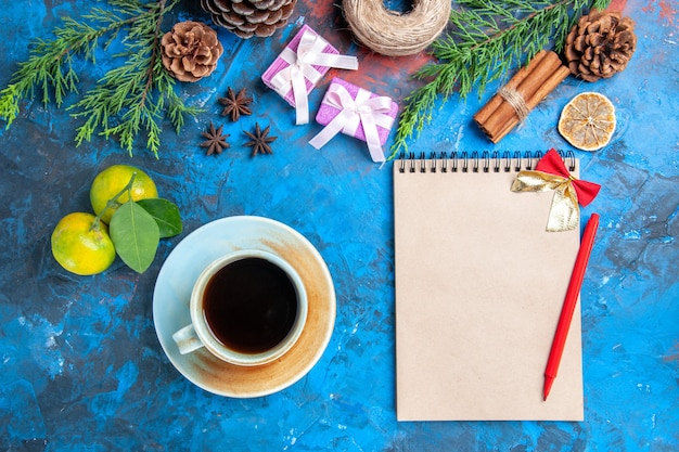 Top view red pen bow a notebook pine tree branches pinecones cinnamon sticks a cup of tea anises straw thread mandarines on blue surface