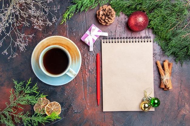 Vista dall'alto penna rossa un taccuino rami di pino albero di natale palla giocattoli bastoncini di cannella una tazza di tè sulla superficie rosso scuro foto di natale