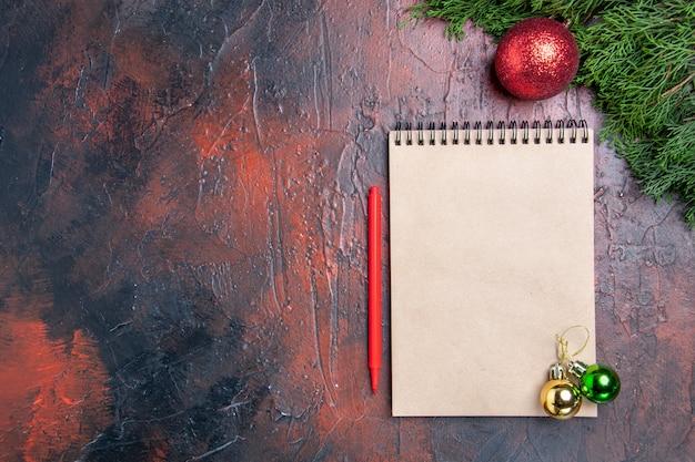 Penna rossa di vista superiore un albero di pino dei rami del taccuino giocattoli della palla dell'albero di natale sullo spazio rosso scuro della copia della superficie