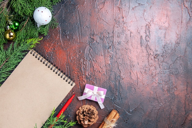 Top view red pen a notebook pine tree branches xmas tree ball toys on dark red surface free space