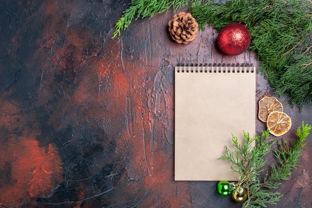 Vista dall'alto penna rossa un taccuino rami di pino albero di natale palla giocattoli fette di limone essiccate una tazza di tè su superficie rosso scuro spazio libero foto di natale