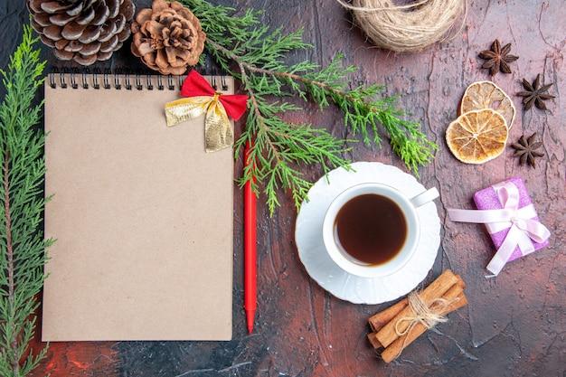 Vista dall'alto penna rossa un quaderno rami di pino albero di natale palla giocattoli e regali una tazza di tè piattino bianco bastoncini di cannella anice su superficie rosso scuro
