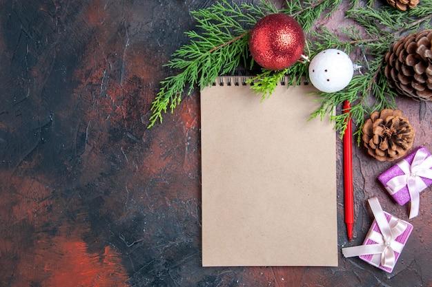 Vista dall'alto penna rossa un taccuino pino rami albero di natale palla giocattoli e regali su spazio libero superficie rosso scuro