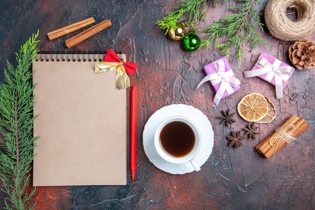 Top view red pen a notebook pine tree branches xmas tree toys and gifts a cup of tea white saucer cinnamon anises on dark red surface