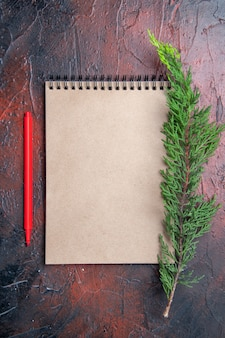 Top view red pen a notebook with small bow a pine tree branch on dark red surface with copy space