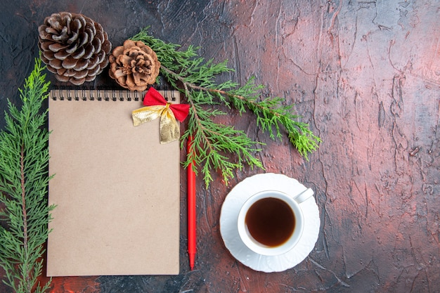 Top view red pen a notebook with small bow pine tree branches pinecones a cup of tea white sauceron dark red surface free space