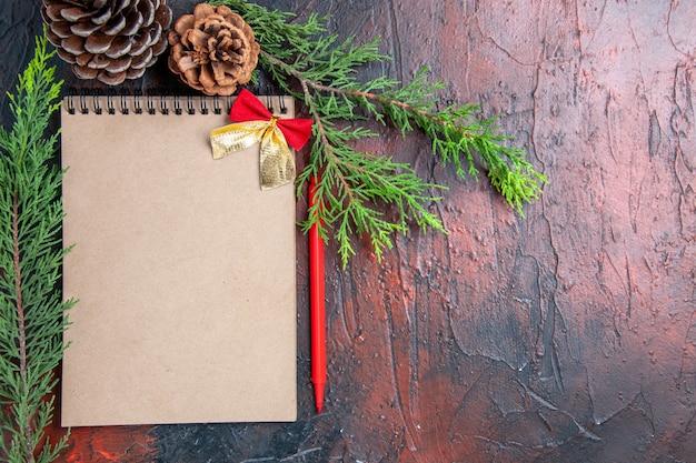 Penna rossa vista dall'alto un taccuino con pigne nelle quali i rami degli alberi di pino con fiocco piccolo su spazio libero superficie rosso scuro