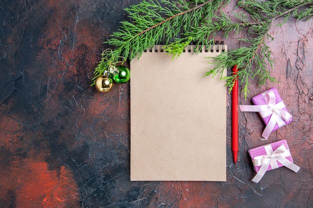 Vista dall'alto penna rossa un blocco note pino rami albero di natale giocattoli e regali su spazio libero superficie rosso scuro