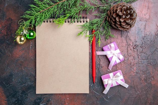 Vista dall'alto penna rossa un blocco note pino rami albero di natale giocattoli e regali pigna sulla superficie rosso scuro