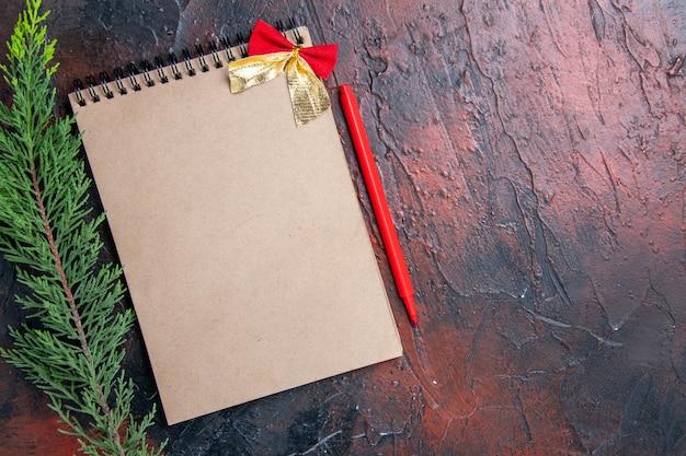 Penna rossa vista dall'alto un blocco note con fiocchetto un ramo di un albero di pino su spazio copia superficie rosso scuro