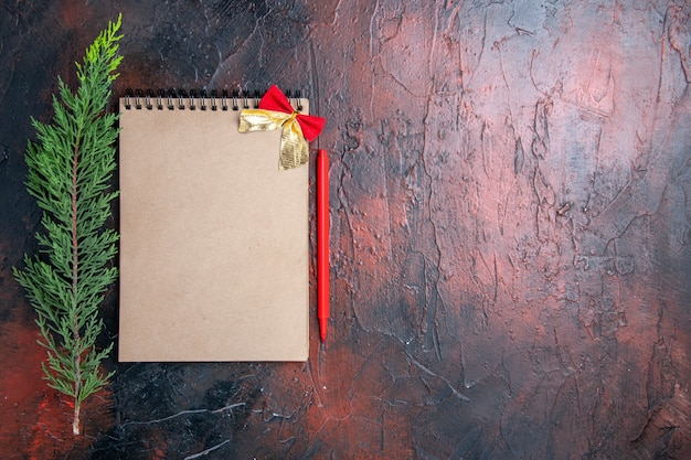 Top view red pen a notepad with little bow a pine tree branch on dark red surface with copy place