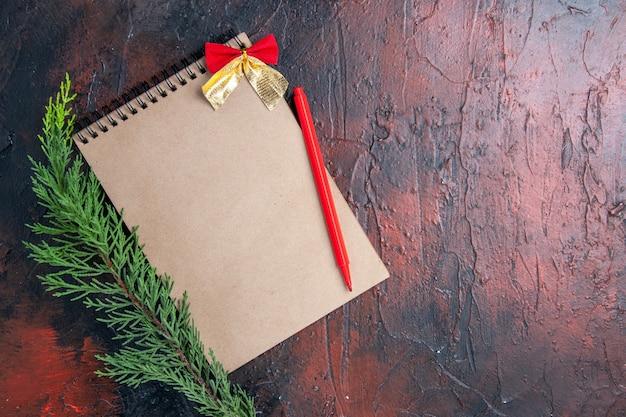 Penna rossa vista dall'alto su un blocco note con fiocco un ramo di un albero di pino su superficie rosso scuro con spazio di copia