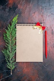 Vista dall'alto penna rossa un blocco note con fiocchetto un ramo di un albero di pino sulla superficie rosso scuro