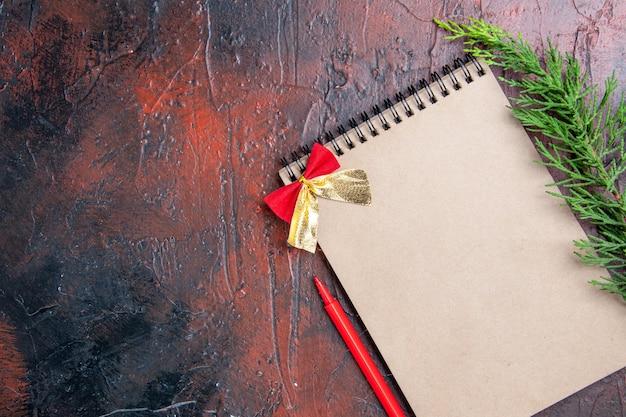 Vista dall'alto penna rossa un blocco note con fiocchetto un ramo di un albero di pino a destra della superficie rosso scuro con spazio di copia