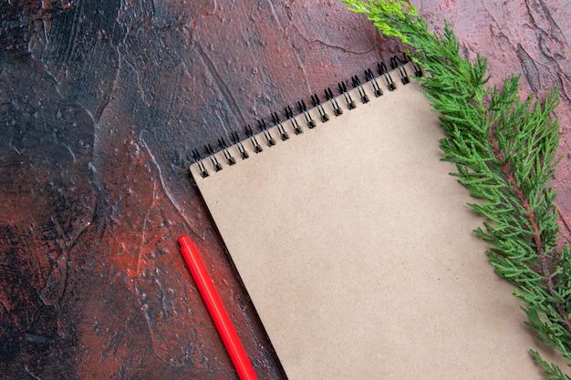 Penna rossa vista dall'alto un blocco note con piccolo fiocco un ramo di un albero di pino su superficie rosso scuro con spazio libero