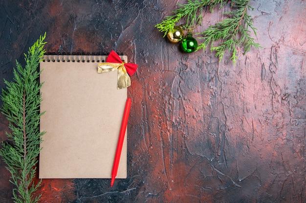 ノートブックの上面の赤いペン松の木の枝暗い赤の表面の空きスペースにクリスマスツリーのボール