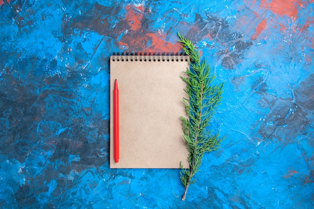 Top view red pencil on a notebook pine tree branch on blue surface free place