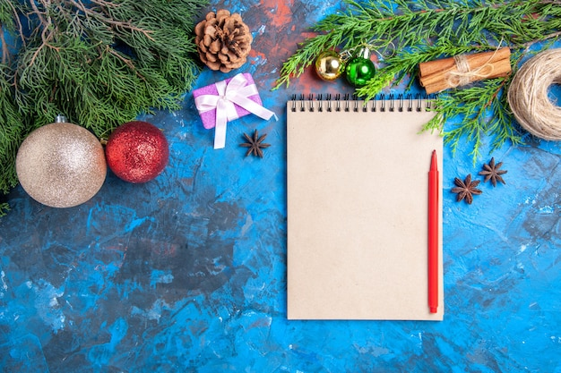 Top view red pencil on a notebook pine tree branches on blue surface with free space