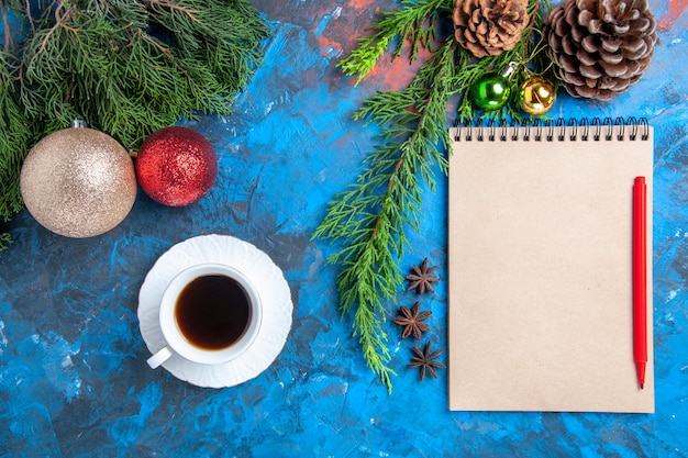 Top view red pencil on a notebook pine tree branches xmas ornaments a cup of tea on blue surface