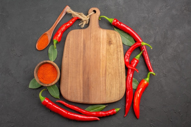 Top view red peppers a chopping board bay leaves a wooden spoon and a bowl of red pepper powder on the black table with copy space