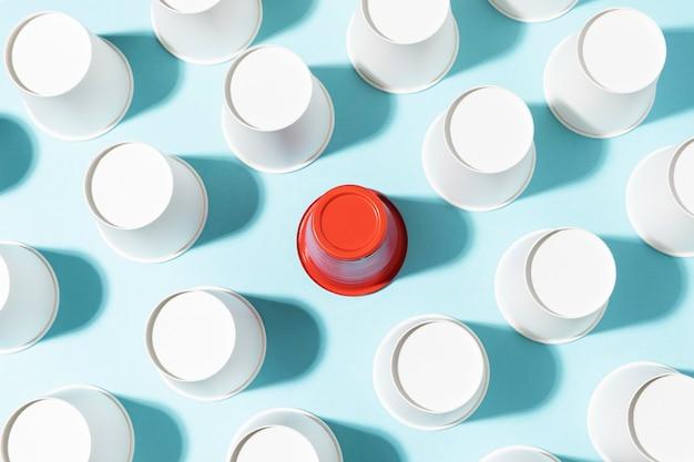 Вид сверху красный пластиковый стаканчик и бумажные стаканчики