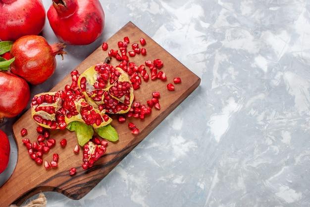 Вид сверху красный гранат свежие и сочные фрукты на белом столе