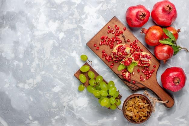 平面図の赤いザクロの新鮮でジューシーな果物と白い机の上のブドウ