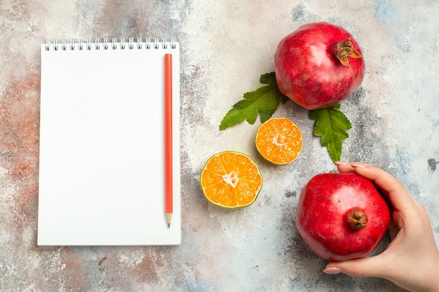 Top view red pomegranates lemon slices red pencil on notebook on nude surface
