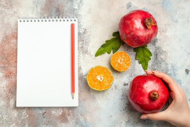 Вид сверху красные гранаты, дольки лимона, красный карандаш на блокноте на обнаженной поверхности