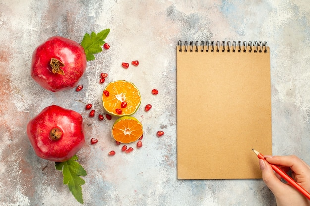 Top view red pomegranates lemon slices red pencil in woman hand notebook on nude surface