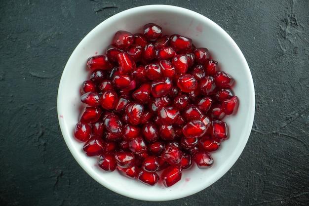 Вид сверху очищенные внутри тарелки красные гранаты на серой поверхности