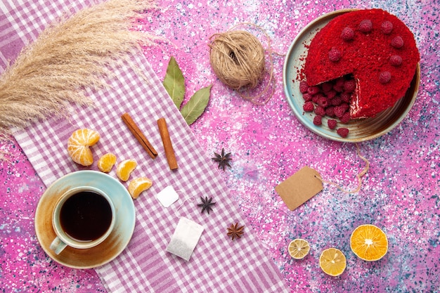 Top view of red raspberry cake with cinnamon tangerines and cup of tea on pink surface