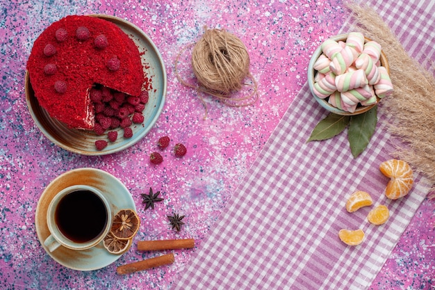 Top view of red raspberry cake with cinnamon and tea on the pink surface