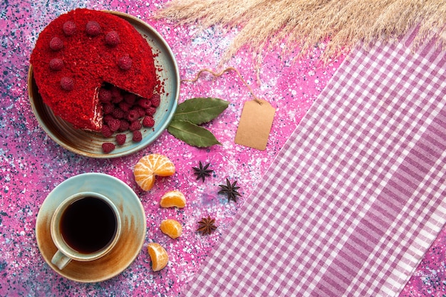 Top view of red raspberry cake with tangerines and tea on pink surface