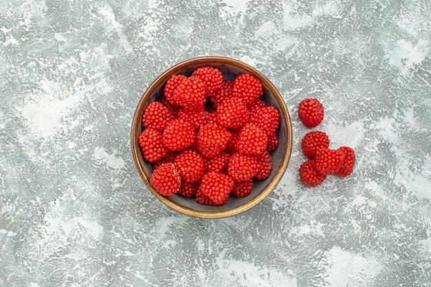 上面図白い背景の上の鍋の中の赤いラズベリーコンフィチュールキャンディーコンフィチュール甘い砂糖茶
