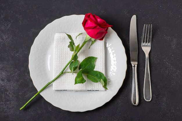 Top view red rose on a plate with cutlery